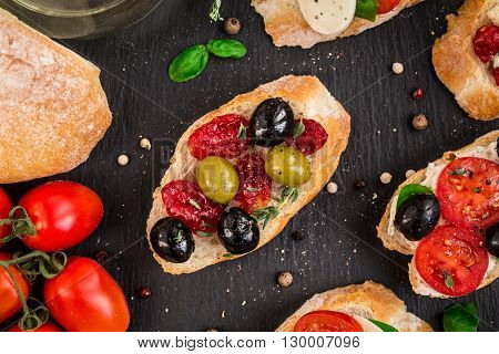 Italian bruschetta with cherry tomatoes, herbs, olives, mozzarella on toasted crusty ciabatta bread
