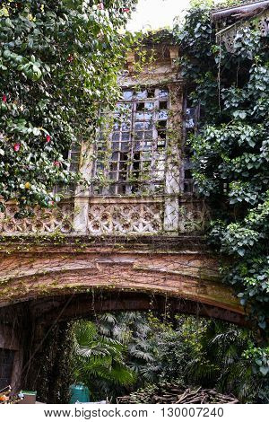 Overgrown abandoned old building with an arch and stained glass windows.