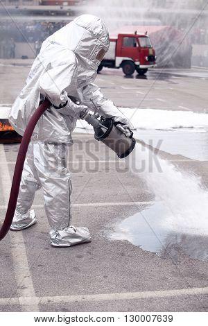 Firemen spraying firefighting foam. Firefighter in action.