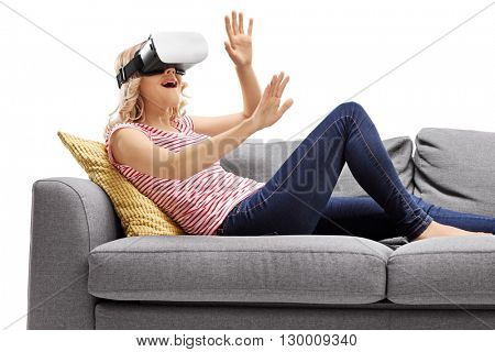 Joyful woman experiencing virtual reality seated on a gray sofa isolated on white background