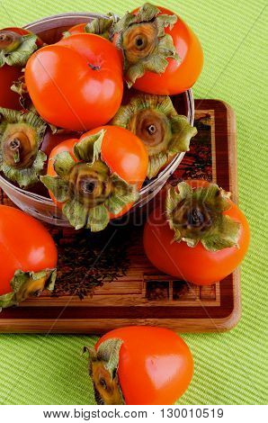 Delicious Raw Persimmon in Wooden Bowl closeup on Wooden Board and Green Textile Napkin background. Top View