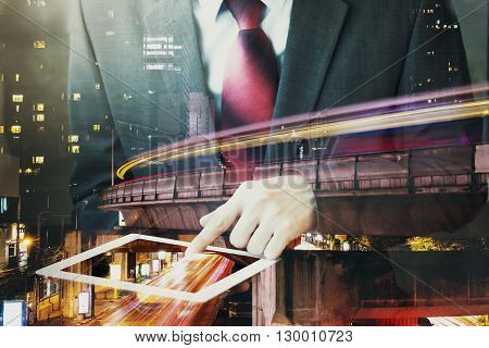 Double Exposure Of Businessman Touching A Tablet In Long Exposure City Scene