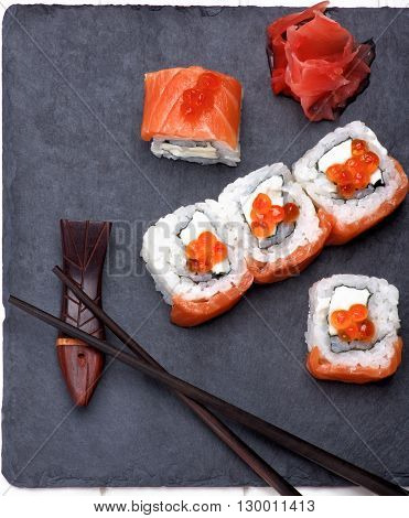 Delicious Sushi with Smoked Sliced Salmon and Gourmet Red Caviar on Stone Plate with Chopsticks and Ginger closeup on White Plank background