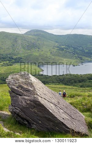 big rock with hikers on the kerry way in irelands wild atlantic way
