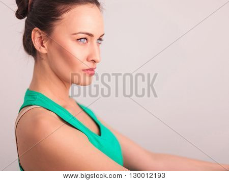side view of a beautiful woman in green undershirt looking away from the camera