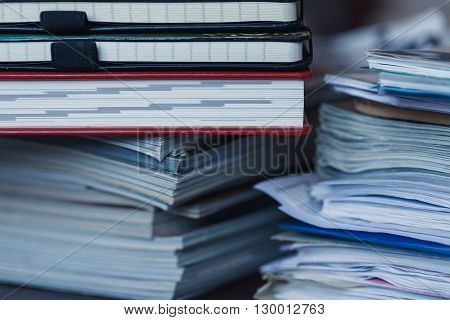 Accounting and taxes. Large pile of magazine notebook and books closeup
