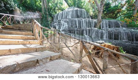 Wide angle view of waterfall and descending stairs at Monasterio de Piedra in Spain, long exposure