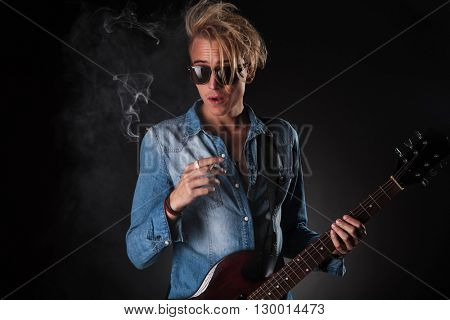 amazed young guitarist smoking cigarette in studio while holding guitar