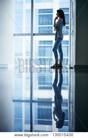 Side view of pensive woman standing in office building at large window