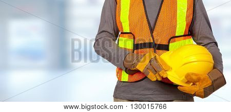 Worker with helmet in orange security vest.