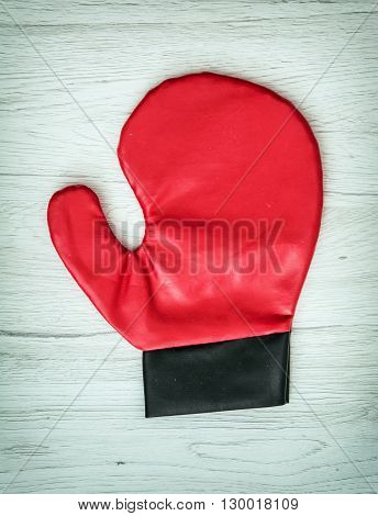 Red boxing glove on the wooden background. Leisure activity. Aggressive sport.