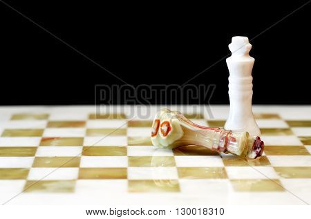 Win concept. One chess Kings lying and other standing on board against dark background