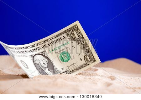 One dollar bank note on sand against blue background