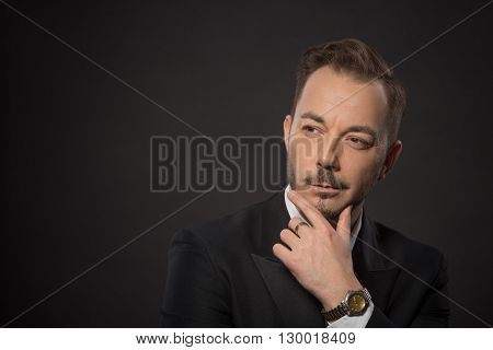 Serious-looking businessman looking away and touching his chin while posing in studio for photographer. Studio shot.