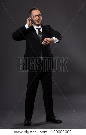Portrait of happy smiling businessman talking over mobile phone while looking at his watch in studio. Handsome man in glasses posing in full length.