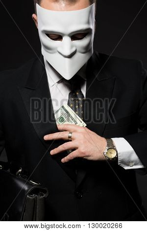 Businessman hiding money in jacket. Man in mask posing with briefcase demonstrating his independence in studio.