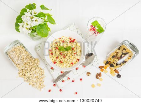 Healthy breakfast with porridge nuts yogurt and pomegranate on white background. Top view