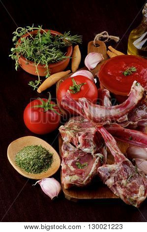 Arrangement of Raw Lamb Ribs with Tomatoes Garlic Herbs Spices and Olive Oil on Wooden Cutting Board closeup on Dark Wooden background