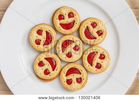 Seven round biscuits smiling faces on the white plate. Humorous food. Tasty cookies. Good mood.