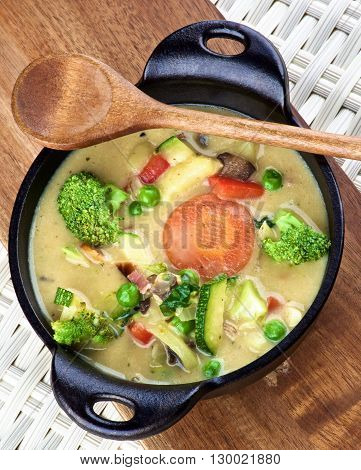 Rustic Vegetables Creamy Soup with Broccoli Carrots Zucchini Leek Red Bell Pepper and Green Pea in Black Iron Stewpot with Wooden Spoon closeup on Wooden Cutting Board. Top View