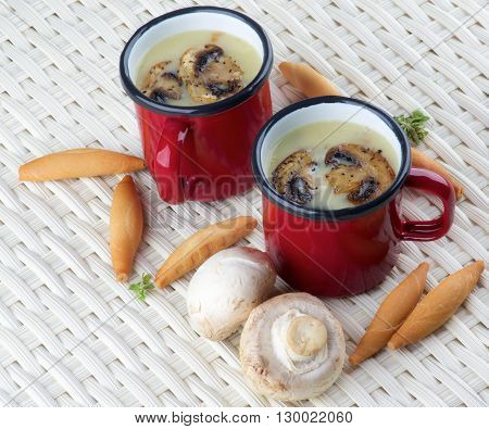 Arrangement of Delicious Homemade Mushrooms Cream Soup Decorated with Roasted Champignons in Red Cups and Bread Sticks closeup on Wicker background