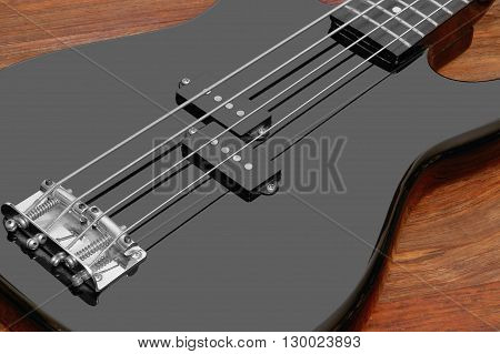 detail of a black bass guitar in brown wooden back
