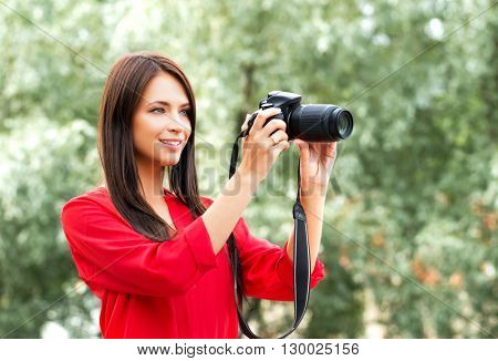 Young beautiful amateur female photographer with new dslr camera in the park.