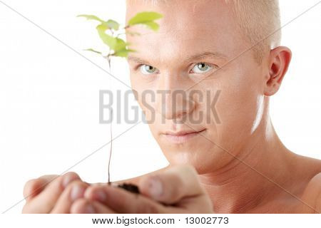Muscular man holding small plant and soil in his hands. Isolated on white in studio.