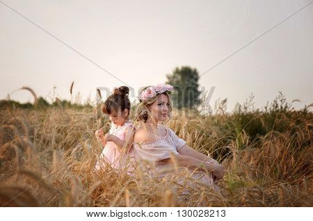 mother and daughter sitting back to back in a field of rye. The daughter looks at spike. Dressed in bright dresses and wreaths