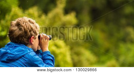 close up of a young boy in a blue coat looking through binoculars at birds with a blurred green background