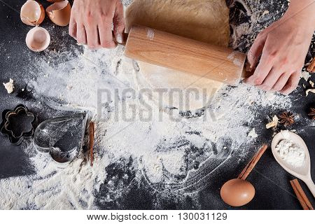 Making of cookies with ingredients like eggs flour cinnamon anise rolling pin paper on blackboard from the top