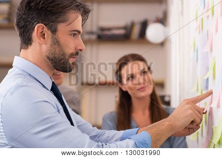 Young creative business team in office taking sticky notes from the wall. Businessman and businesswoman looking at post it on wall in office. Man looking sticking notes on wall in creative office.