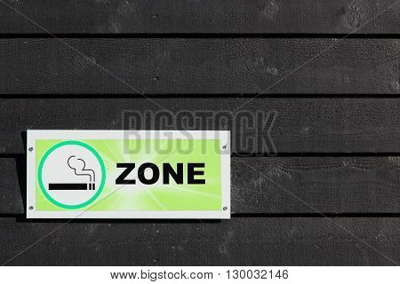 Smoking area sign against a wooden wall