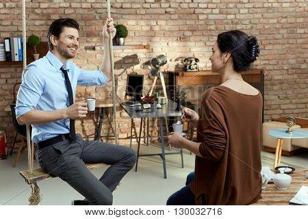 Young businesspeople talking in modern office, businessman sitting on swing, smiling.