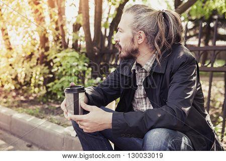 Bearded Asian Man Sitting On Sidewalk In Park