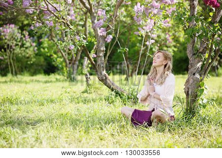 Woman meditates in the lotus position under a bush blooming lilac