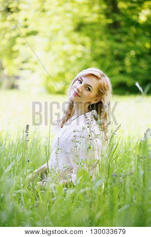 Young beautiful girl sitting in the grass