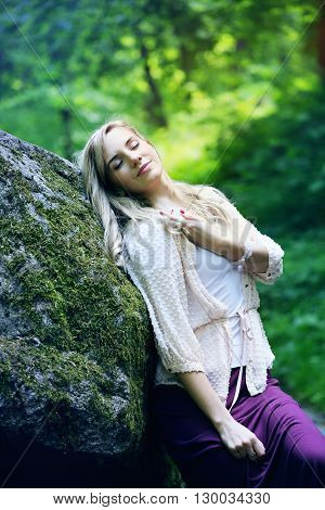 beautiful young girl resting in a forest on the rock