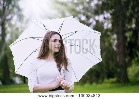 Beautiful girl with white umbrella walking through a meadow
