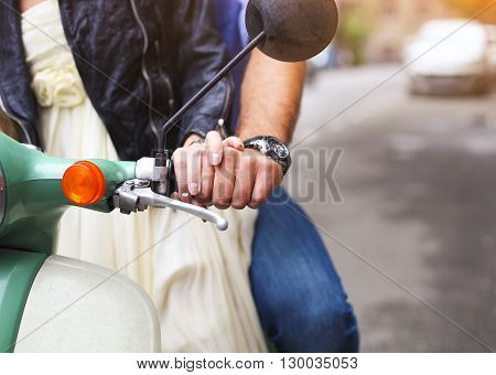 Happy young couple riding a vintage scooter in the street. Closeup. Holiday and travel concept
