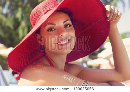 Young brunette fashionable woman in red hat posing in a red bikini