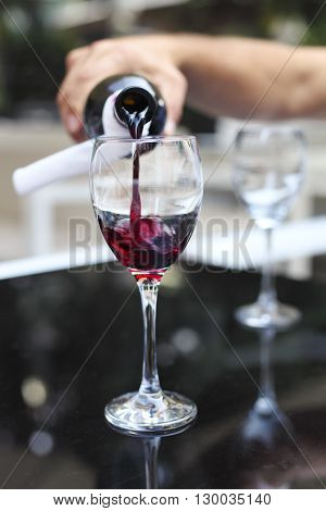 Pouring red wine from bottle into the wineglass in outdoor restaurant