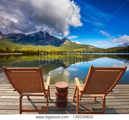 Two comfortable wooden sun beds for tourists, interconnected table. Pyramid Mountain reflected in Pyramid Lake