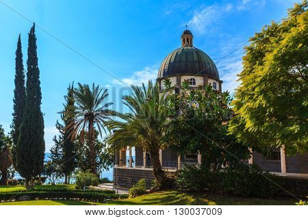 Israel, the shores of Lake Kinneret. Catholic monastery and small church Mount Beatitudes. Dome and colonnade surrounded by cypress and palm trees.