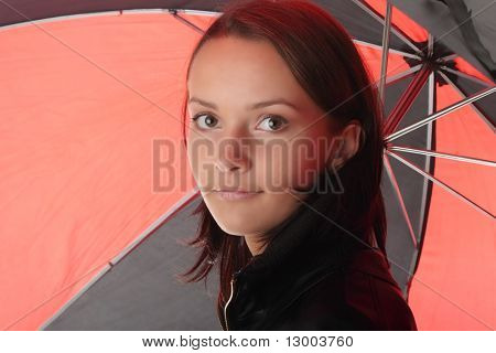 Beautiful teen woman dressed in black under red and black umbrella isolated on white background