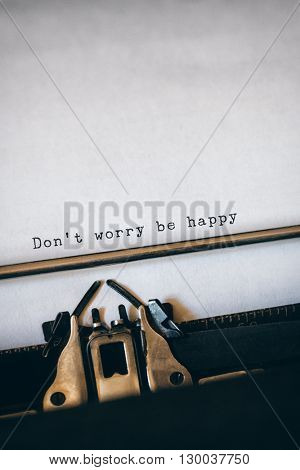 Don't worry be happy message on a white background against close-up of typewriter