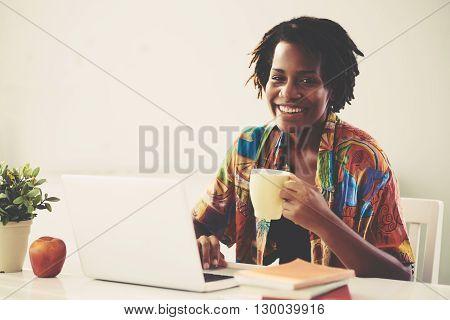 Happy African-American woman having short coffee break