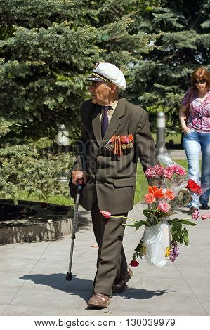 Kyiv, Ukraine - May 8, 2009: Senior veteran carries a bouquet of flowers during Victory Day celebration at the Museum of The History of Ukraine in World War II in Kyiv