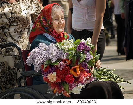 Kyiv, Ukraine - May 8, 2009: Senior veteran woman on a wheelchair holds a bouquet of flowers during Victory Day celebration at the Museum of The History of Ukraine in World War II in Kyiv
