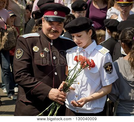 Kyiv, Ukraine - May 8, 2009: Male cossack officer presents his female counterpart with bouquet of flowers during Victory Day celebration in Kyiv